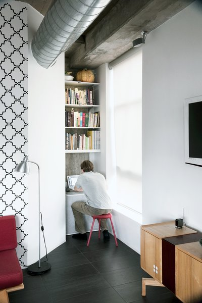 Arthur installed shelving from Ikea and poured a cast-in-place concrete shelf to create a small media nook.