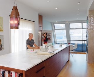 Vintage pendants cast a soft glow over the island, which contains a Bosch dishwasher.