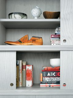A Clean Slate - Photo 3 of 5 - The cabinet doors of the living room wall unit, in birch veneer painted a calming gray, slide with silken ease but never fully close, leaving strategic gaps for the display of Jun's eclectic array of books and objects.