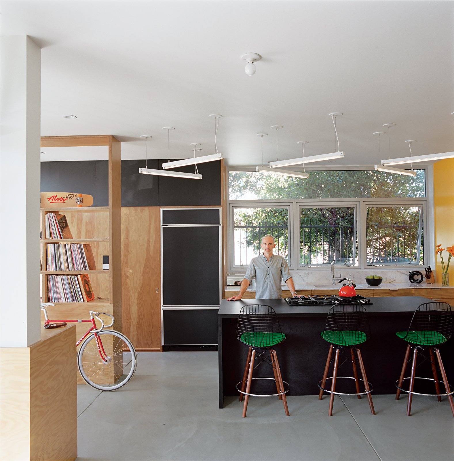 """The """"murdered kitchen"""" includes a fluorescent light sculpture with dimmable ballasts designed by Bestor. The rough plywood offers a nice chromatic contrast.  Photo 5 of 11 in Daft Punk Could Play at This House"""