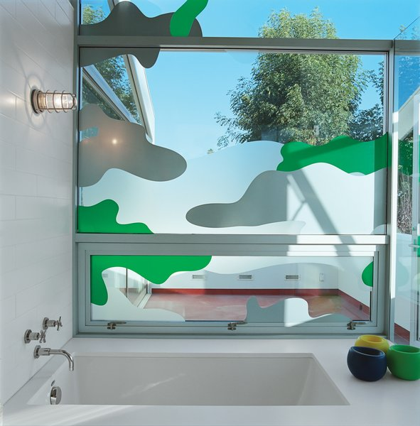 "Los Angeles–based graphic designer Chris Loomis created a trio of window decals for the house's three bathrooms. Grunbaum went with a camouflage pattern for privacy in the master bathroom, which has a wall of floor-to-ceiling glass that looks onto an adjacent patio. ""Because we're sort of in the trees, I wanted to keep the plant theme going,"" he says. laloomis.com"
