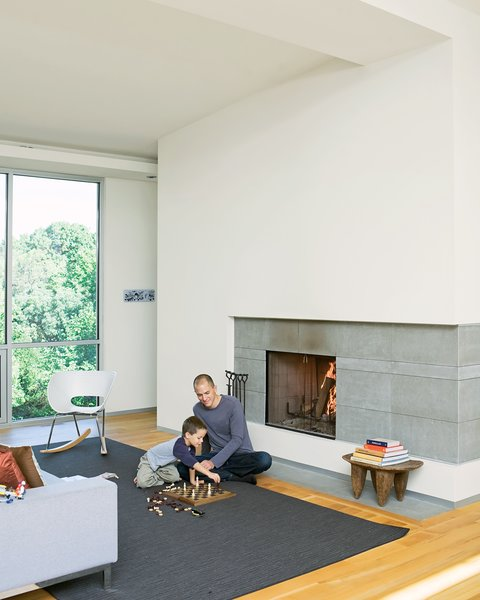 Christian and Jack play chess by the fireplace - the centerpiece of the living room and which the Arnolds use daily during the winter. The hearth is made of large slabs <br><br>of limestone, which Christian cut himself, intentionally leaving imperfections on the surface for texture. A studio8 couch and Vitra Tom Vac Rocker articulate the space.