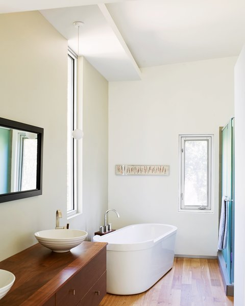 The Duravit tub in the master bathroom is another favorite spot for keeping warm; it offers a slender view out toward the trees.