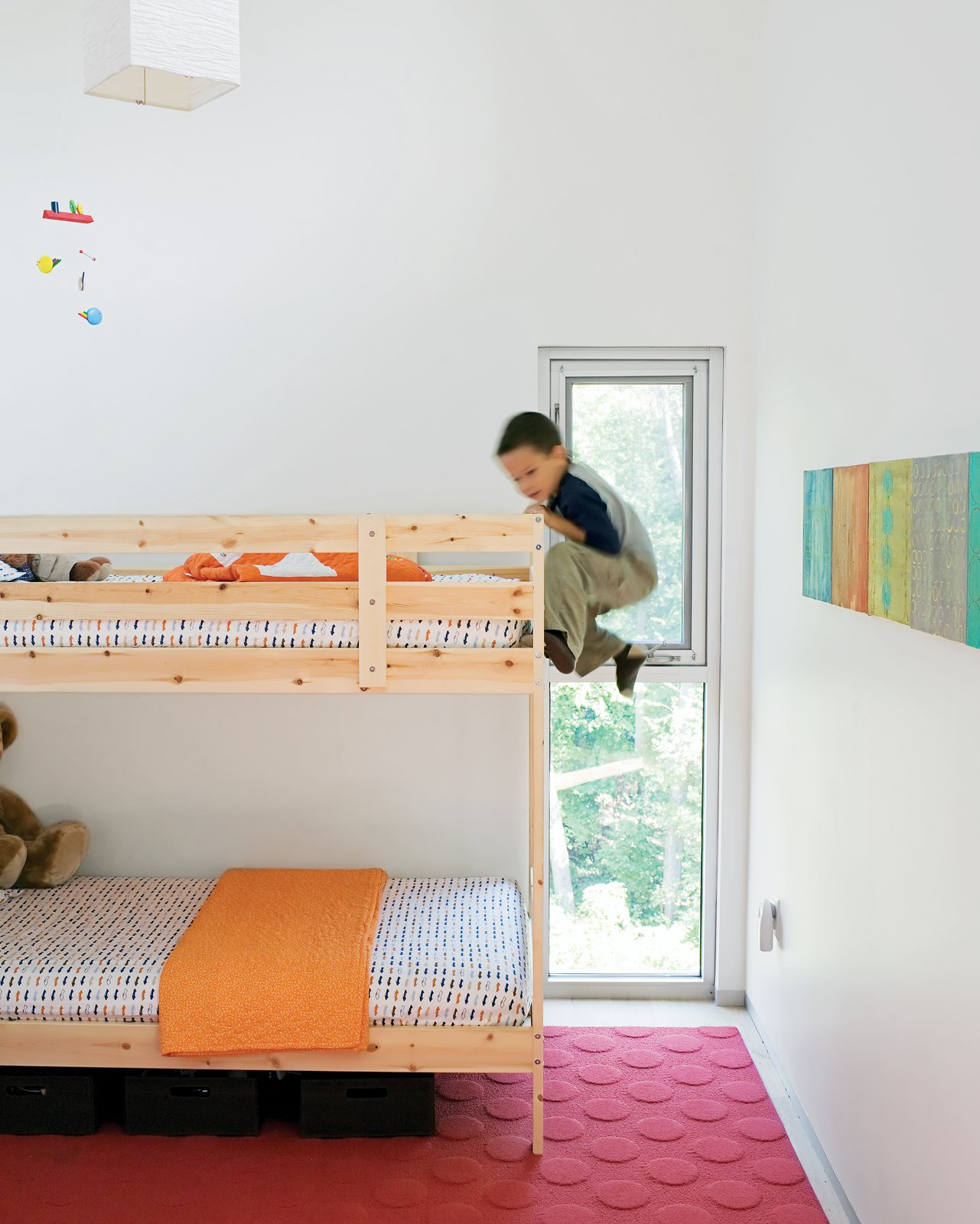 In the kids' room, Jack climbs the bunk bed he shares with his little brother, James. The paintings on the wall were done by their mom. Tagged: Kids Room, Bedroom, and Bunks.  Photo 7 of 7 in A Lot to Love
