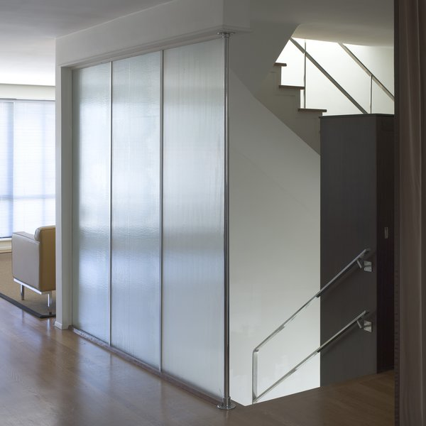 Glass panels surrounding the stairwell allow a nice amount of gentle light into the living room. Photo by Mark Darley.