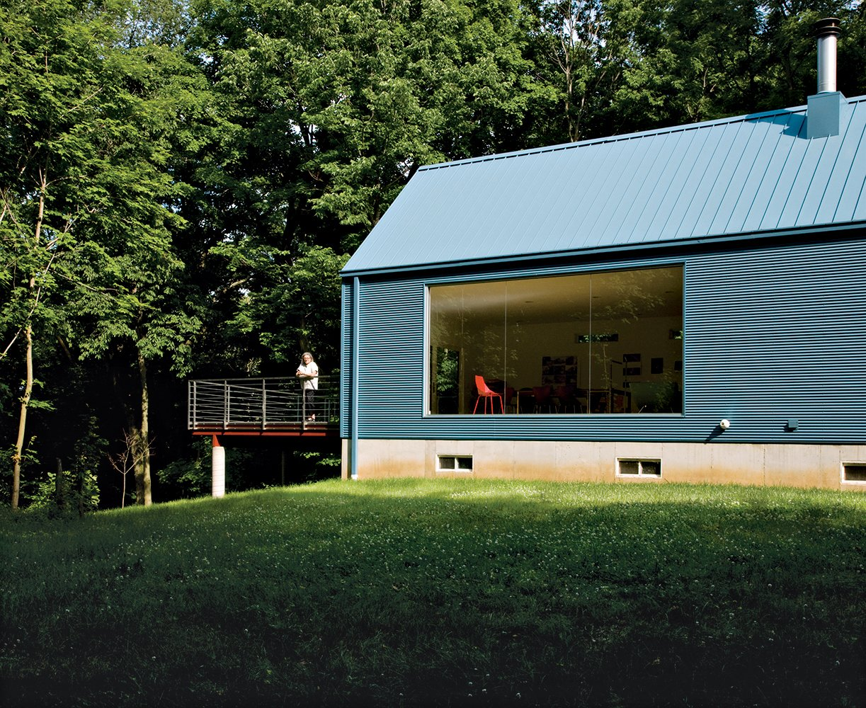 The floor-to-ceiling living-room window was inspired by Philip Johnson's Glass House. Tagged: Exterior, House, Metal Roof Material, and Metal Siding Material.  Photo 6 of 10 in Bringing It All Back Home