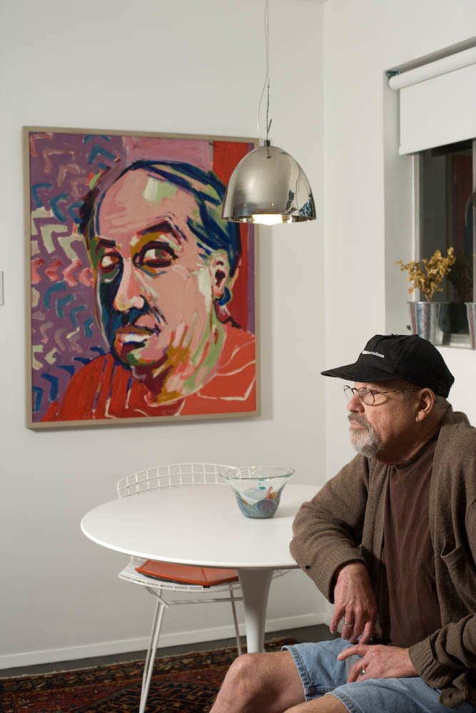 Ronald Popp, with a self-portrait in the dining zone off the kitchen. The Harry Bertoia chairs are from his existing collection; their orange pads served as the design springboard for the kitchen cabinetry. Popp acquired the Eero Saarinen table for the space.  Photo 6 of 6 in Renovation: 800 Square Feet