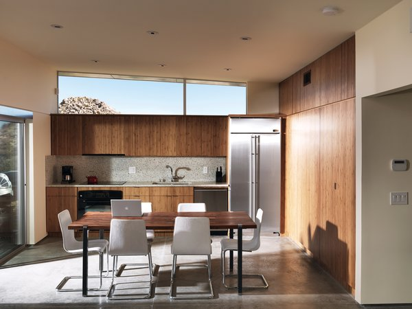 One large room houses the kitchen, dining, and living area; the backsplash and countertops are made by Vetrazzo.
