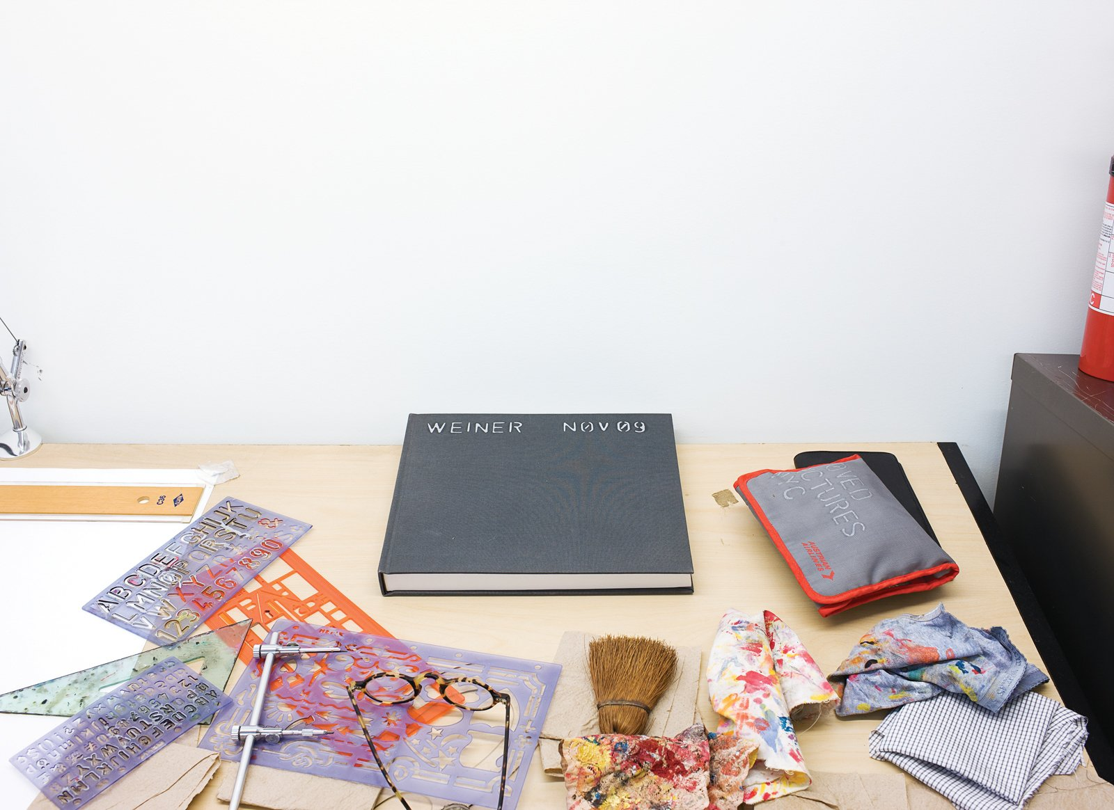 A collection of objects from Lawrence's desk include stencils, paint rags, glasses, and a notebook. Tagged: Office, Study, and Desk. Village People - Photo 4 of 13