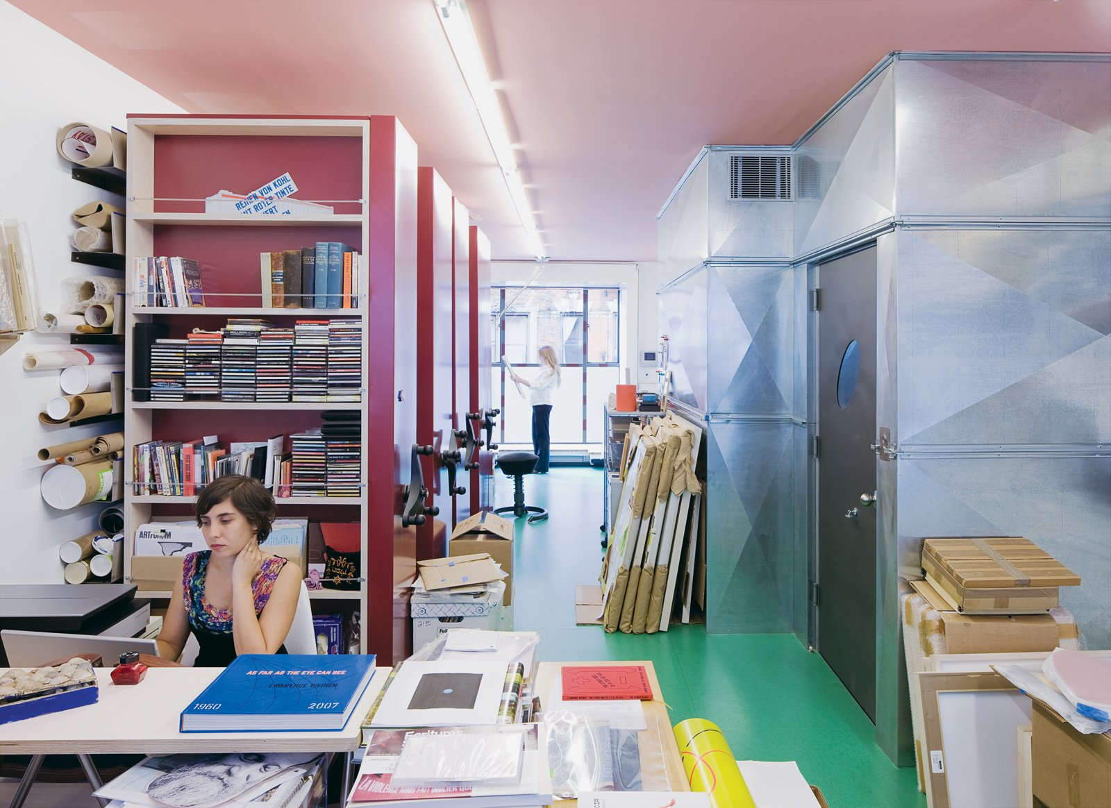 The couple's archival photographer Alyssa Gorelick sits in front of Lawrence's sliding red storage units while Alice reviews some papers in the background.  Photo 8 of 13 in Village People