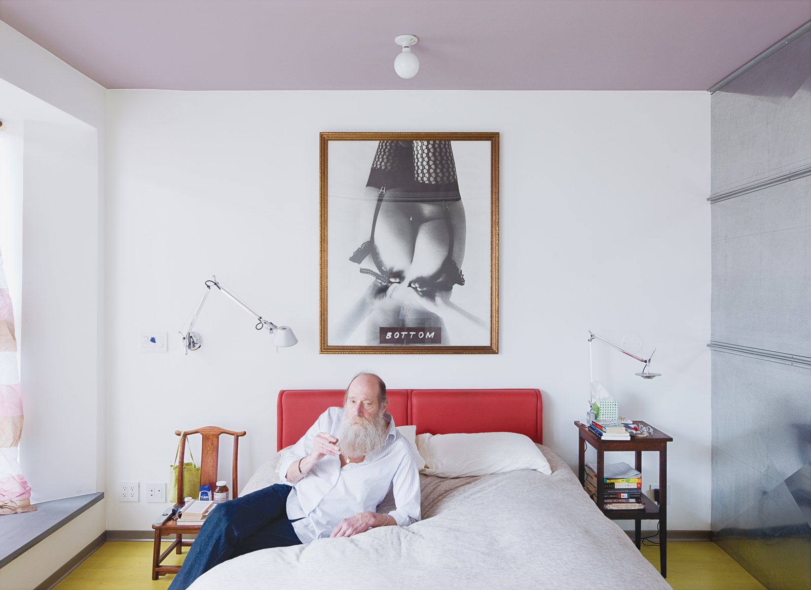 Lawrence relaxes in the master bedroom with a hand-rolled cigarette. The room   has a lavender ceiling (Alice was told it's the best color to see when waking). Tagged: Bedroom, Bed, Wall Lighting, and Night Stands.  Photo 10 of 13 in Village People