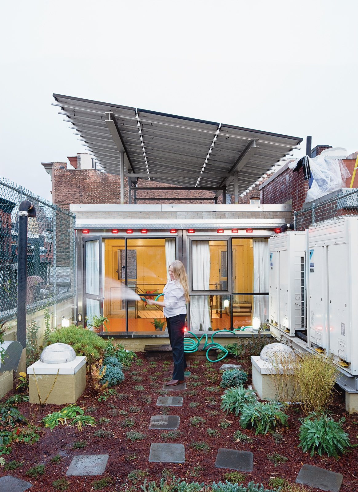 The Weiners' first stab at a decorative green roof went awry when workers installed the fabric membrane incorrectly; the plants didn't thrive, and   soil leached down the drain, causing a backup in the yard below. But with the help of an artist friend—–and avid gardener—–they successfully brought a piece of cultivated wildness, including hardy flora like creeping thyme, honeysuckle, hops, and kiwi, to their roof.  Photo 1 of 13 in Village People