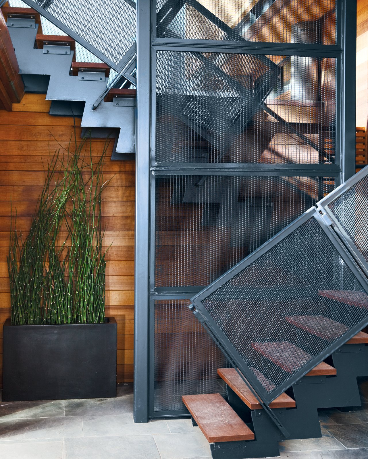 The steel stairwell that connects the garden-level patio with the new living space performs double duty as an anchor attached to the foundation. A Modern Coastal Home in Stinson Beach - Photo 8 of 10