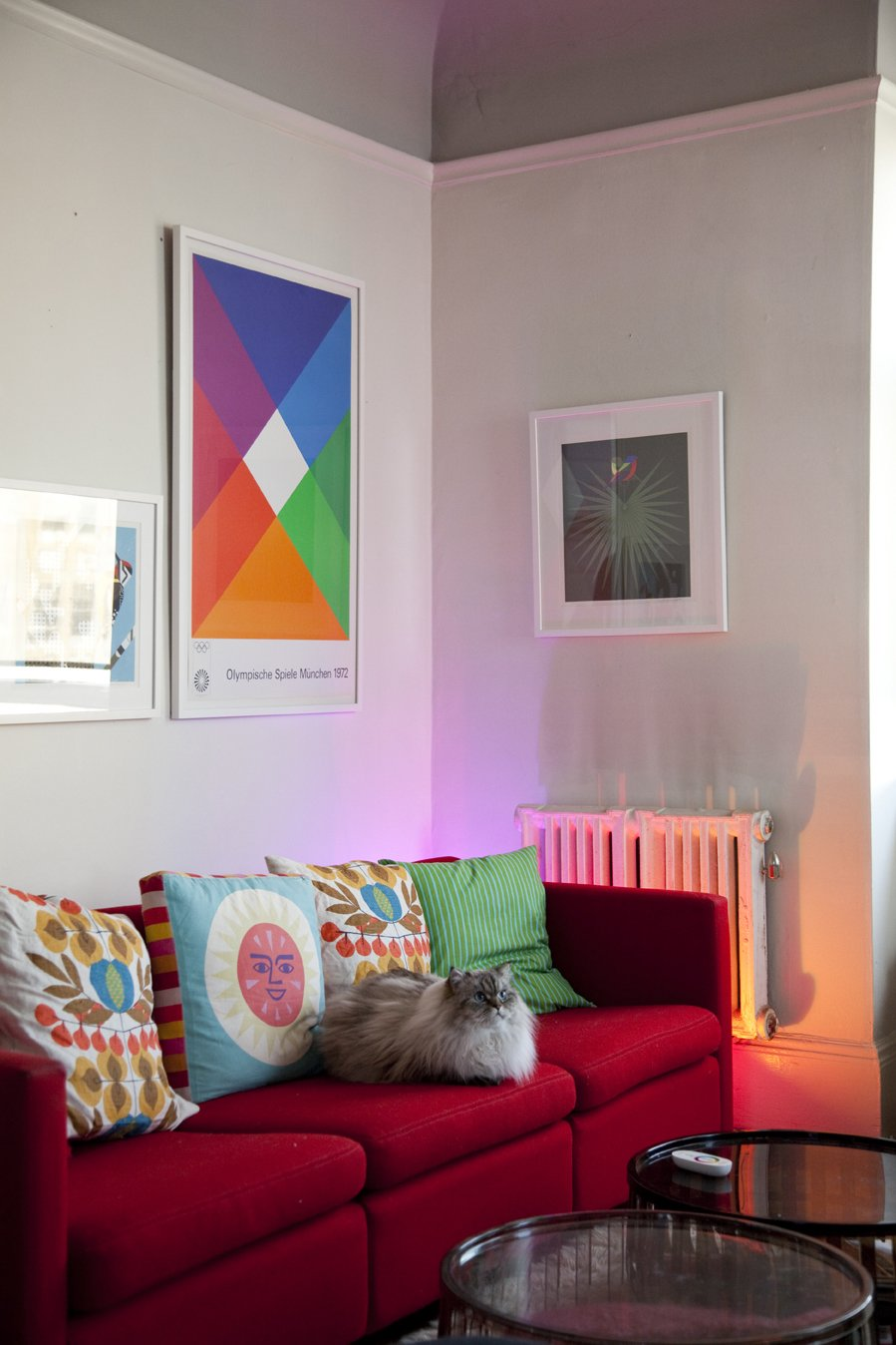 In the living room, the LivingColors lamp, though obscured from view by a Knoll sofa by Charles Pfister, mimics the bright warm tones of the Max Bill poster. Grawe's cat, Eero, settles in amongst a collection of both vintage and contemporary pillows.  Photo 4 of 21 in 21 Cats Living in the Modern World from Cats–At Home in the Meow-dern World