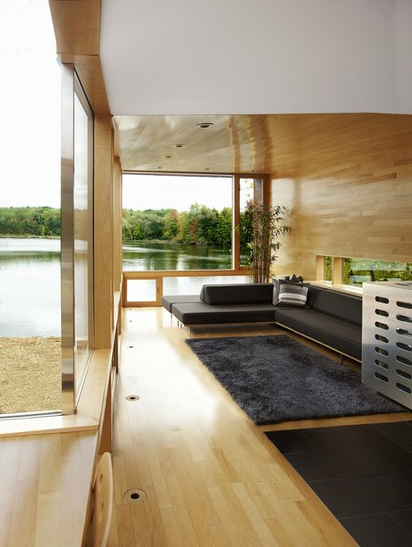 The living area overlooking the lake includes a banquette that seats eight and sleeps three, upholstered with a fully compostable Climatex Lifecycle fabric. A low-slung horizontal side window allows a sliver of light in yet retains privacy.