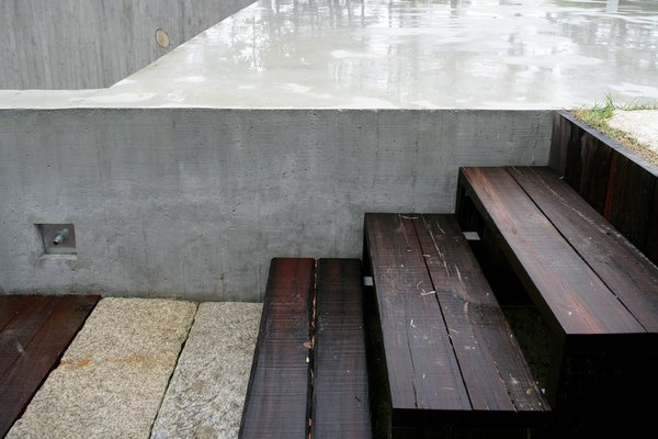 The juxtaposition of raw wood, stone, and concrete brings out the beauty of each material.