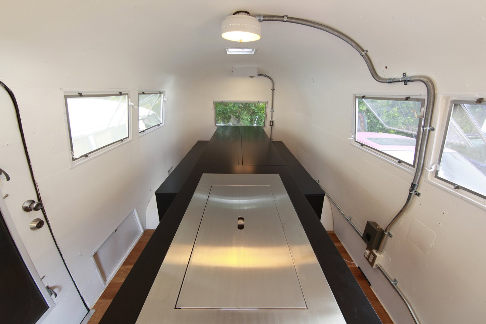 To maximize the small space inside the Airstream, Suzuki removed the existing structures and added a central island the follows his kenchikukagu style of design. Near the door (front of photo), a sink and cook top is hidden under the steel cover. At the rear (back of the photo), a dining table transforms into a set of twin beds. Photo by Sadamu Saito.  Photo 1 of 10 in Hide and Sleep