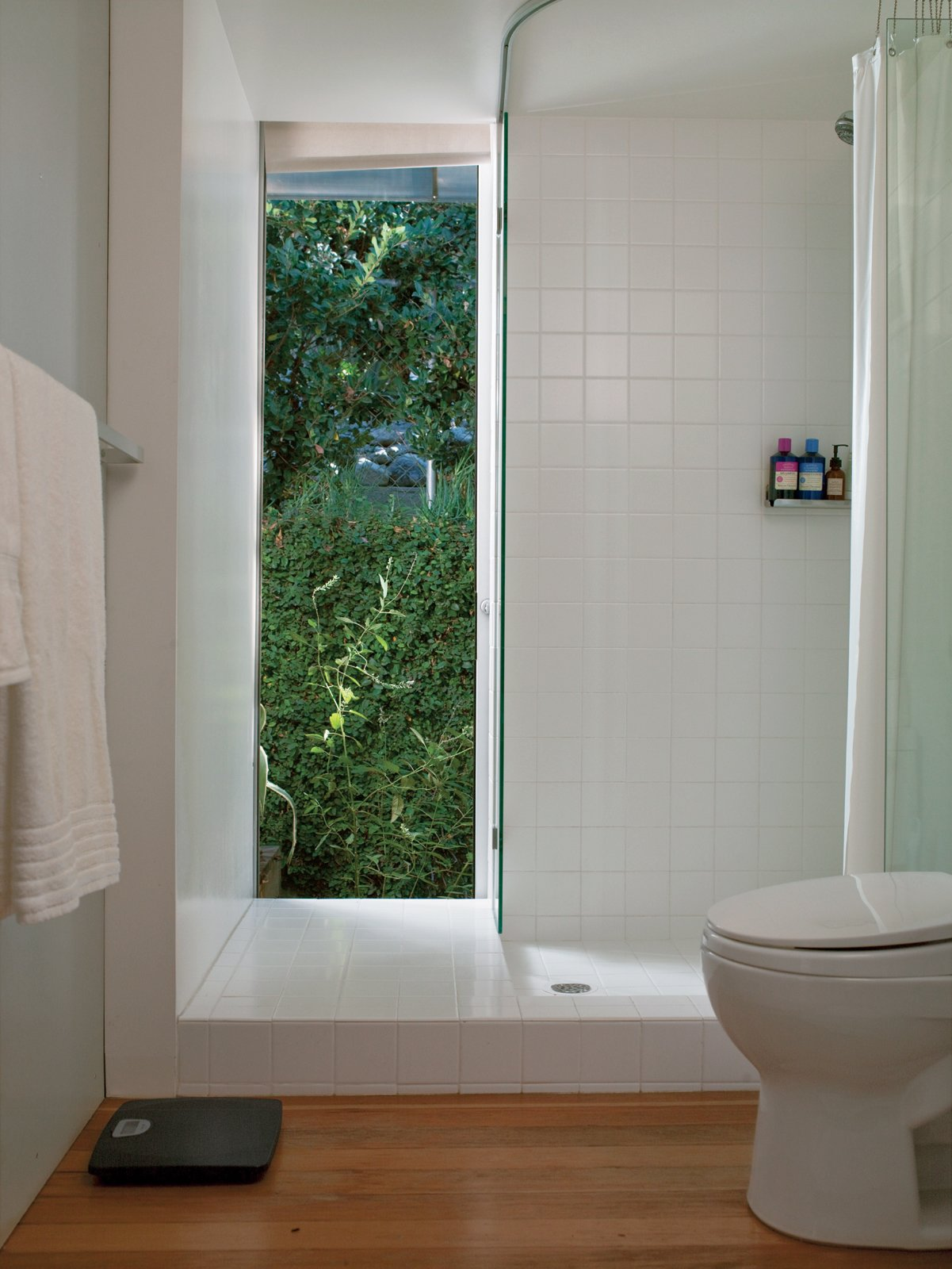 At $2.75 a square foot (which includes a designer discount), Molina and Turin could afford to extend matte white ceramic tiles from Dal-Tile beyond   the conventional shower boundaries to give the bathroom the look of   a brighter, more expansive space.  Photo 9 of 11 in How Good Idea Studio Revamped a 1924 Clapboard House on a $62,000 Budget