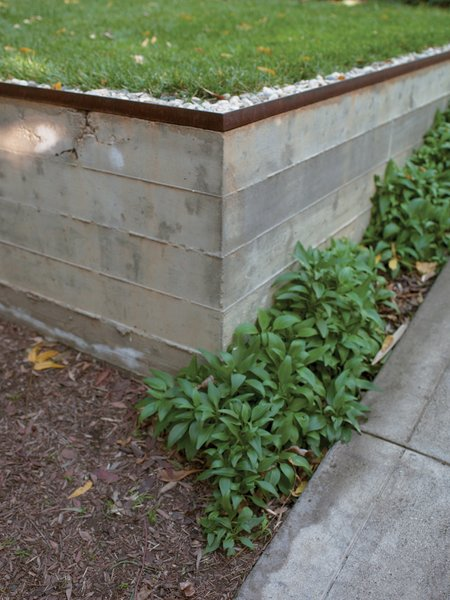 Concrete retaining walls form an outdoor terrace that serves as a dining area, conference room, and workshop. The three-quarter-inch construction gravel from George L. Throop Company allows rain to percolate into the ground and irrigate a lemon tree rather than create polluting runoff.
