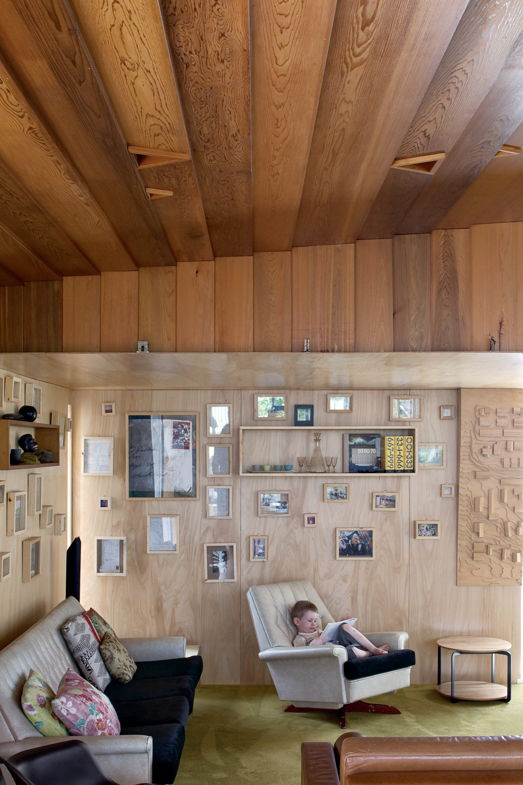 Four-year-old Seamus relaxes in the living room, whose plywood walls   are covered with family photographs. Tagged: Living Room, Sofa, Recliner, and Chair.  Photo 8 of 11 in The Great Compression