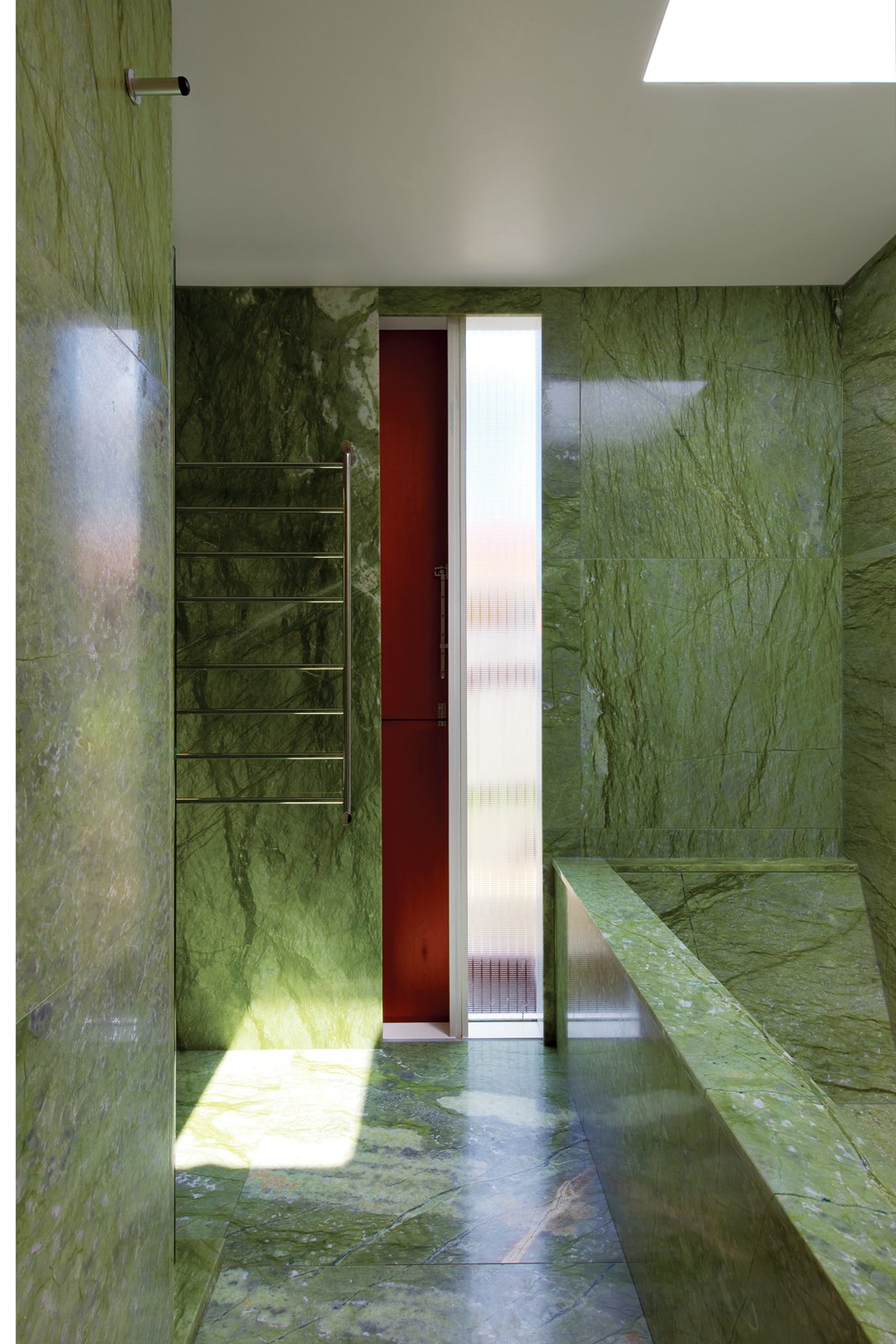 The tiny budget still allowed room for some strategic splurges, such as the vivid green Verde Ming marble in the house's only bathroom