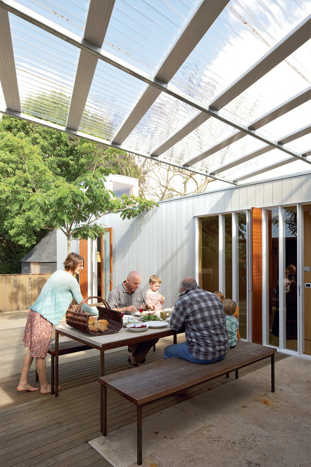 The family shares an alfresco lunch with Ikimau Ikimau, a friendly neighbor who helped build the house. The aluminum weatherboard cladding was custom-designed by O'Sullivan. Tagged: Outdoor and Wood Patio, Porch, Deck.  Photo 11 of 11 in The Great Compression