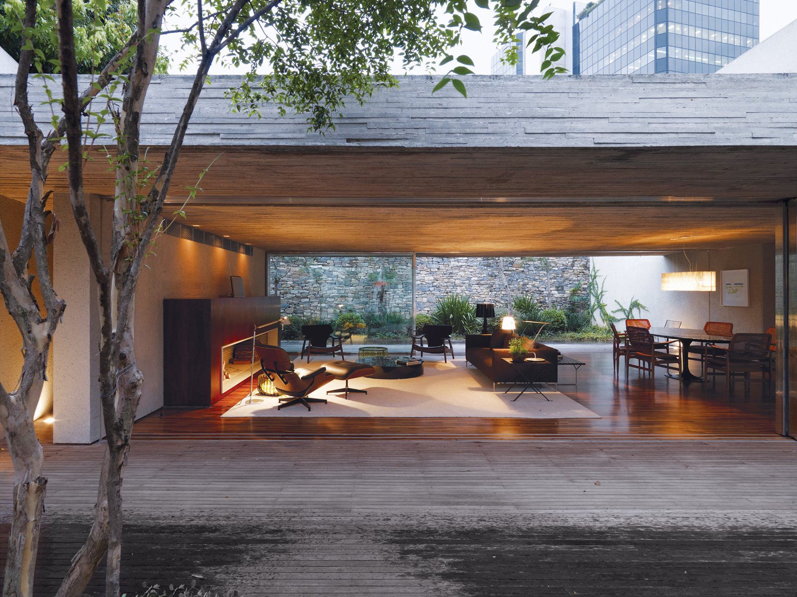 By keeping the front and back gardens at the same elevation as the living area, Kogan created one giant living space. A large overhang means that even on a rainy day, the Cósers can live practically without walls. The dining area is defined by a classic Oval dining table by Eero Saarinen for Knoll. Brazilian master designer Sergio Rodrigues did the matching pair of armchairs in the living room.  Homes Blending Indoor and Outdoor Living Space by Megan Hamaker from São Paulo, Brazil
