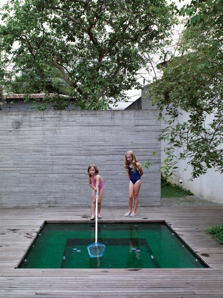 Sophia supervises her sister Helena as she cleans the surface of the small pool, whose rich emerald tiles echo the luxuriant greens of the garden's tropical plantings.