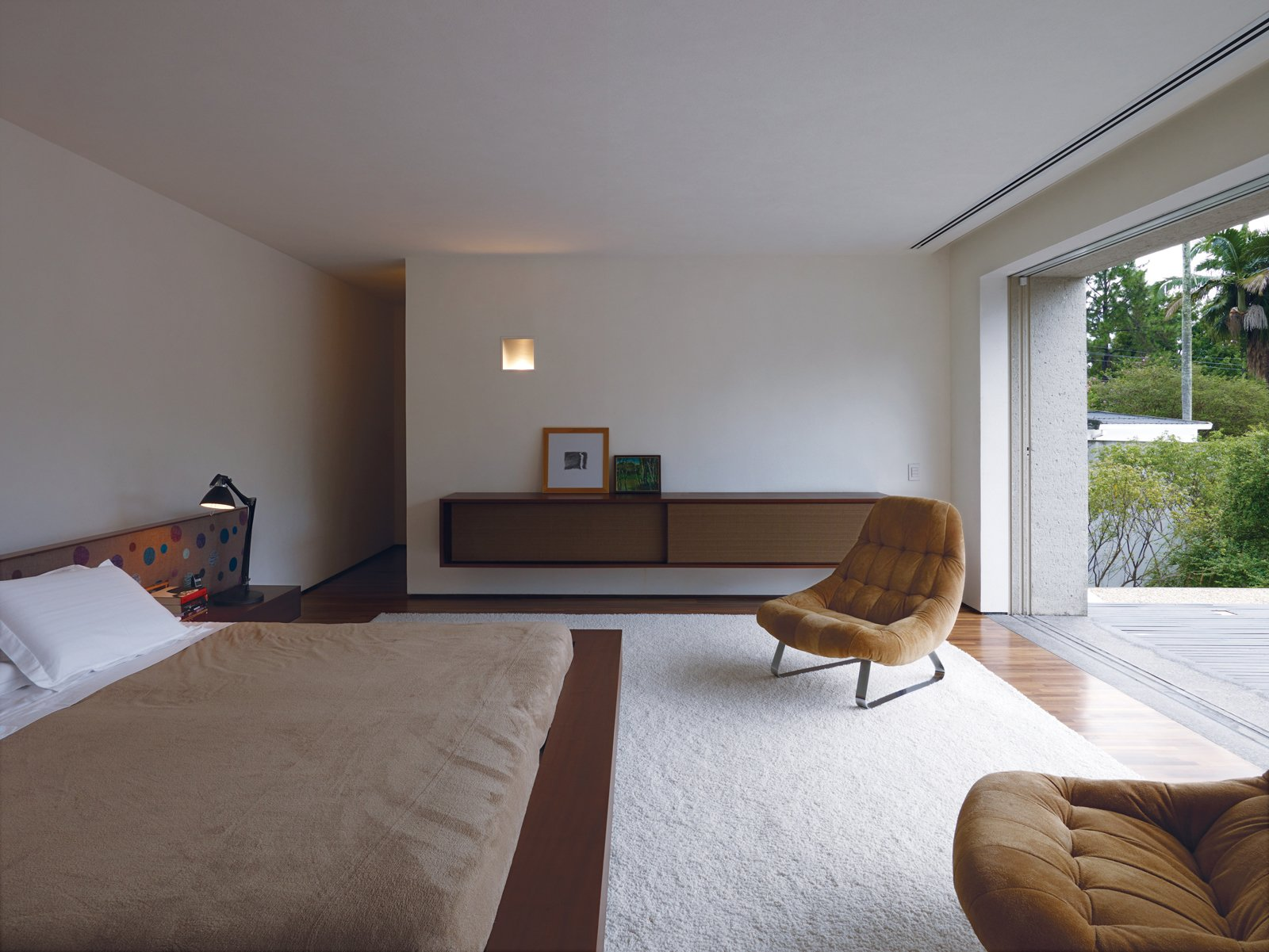 Kogan designed a number of the built-in furnishings, including the headboard and cupboard in the master bedroom.The cupboard is deliberately reminiscent of a mid-century stereo speaker. The vintage lounge chairs are by Percival Lafer.  Modern Bedroom Ideas  by Matthew Keeshin from São Paulo, Brazil