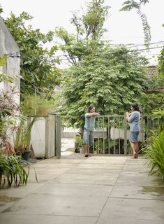 Humid City, Cool Home - Photo 14 of 26 - Wisnu and Sundari have a chat at the gate, which just barely keeps Jakarta's heavy vegetation at bay.