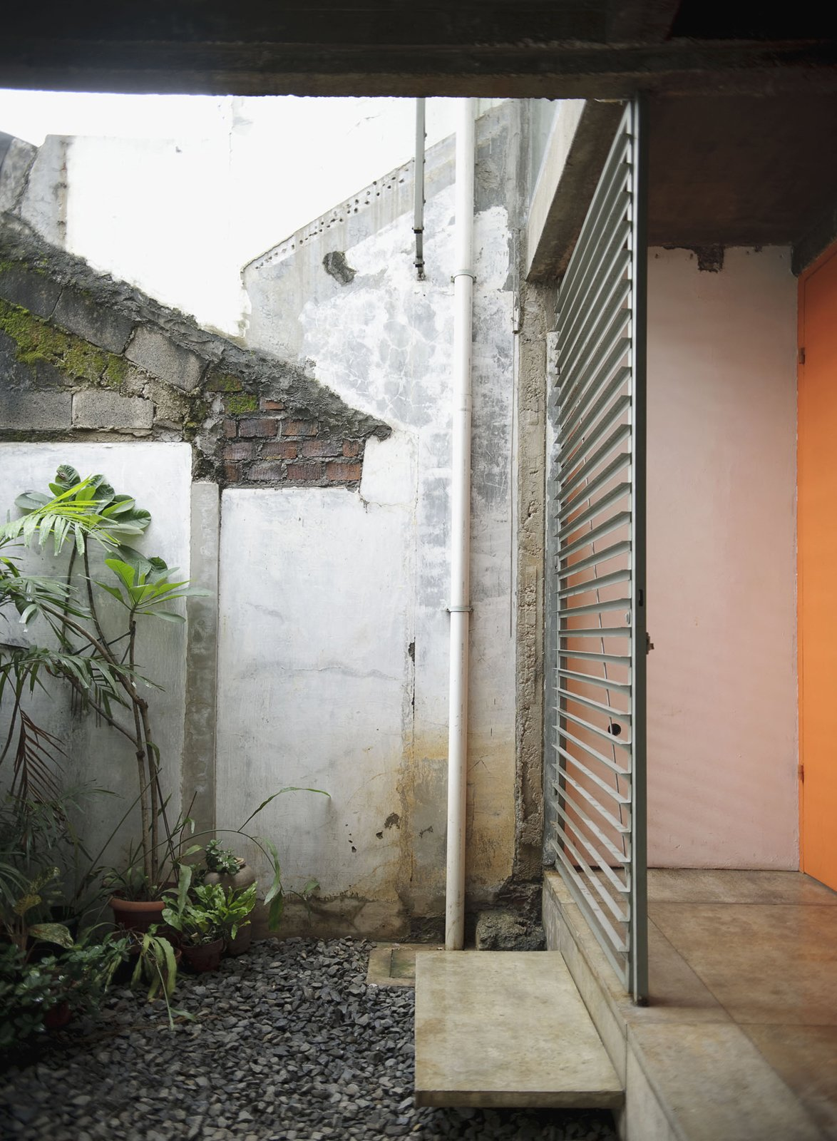 An orange door and metal grille make for a warm, if industrial, contrast to the stones and plants on the patio. They also weather well, something critical in a place where the climate leads to a palpable sense of decay. Humid City, Cool Home - Photo 17 of 26