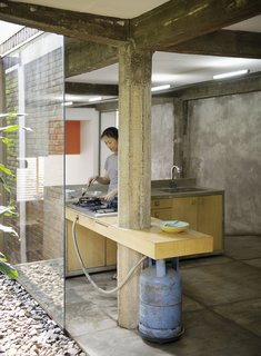 """Humid City, Cool Home - Photo 21 of 26 - Here Sundari puts a bit of food together in the kitchen. A gas-fired grill and concrete countertop give the place a rough-hewn feel, and certainly evokes architect Ahmad Juhara's rally cray, """"Ad hocism is my religion."""""""
