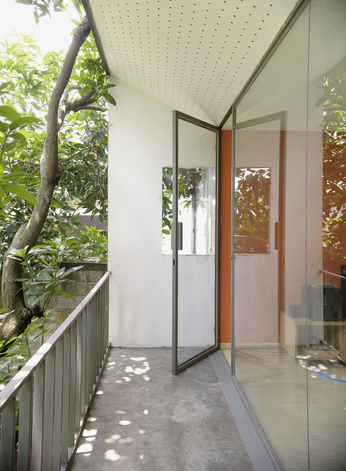 That orange accent is carried from a door downstairs to the family room upstairs and a glazed facade keeps things very bright indeed.  Photo 24 of 26 in Humid City, Cool Home