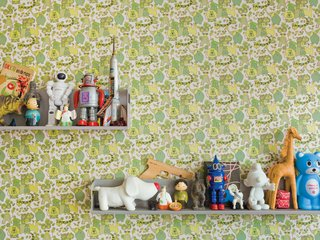 "Because their home is a rental, De Waart was limited in the changes she could make. In the boys' room, she added vintage wallpaper. ""From a distance it appears to be all shades of green but when you have a closer look, it turns out to be one big jungle,"" De Waart says. She covered just a single wall with the paper to keep the room from feeling overrun with color."