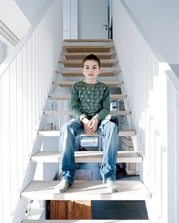 Axel sits on the staircase, which like all the internal and external cladding in the house is made from Douglas fir.