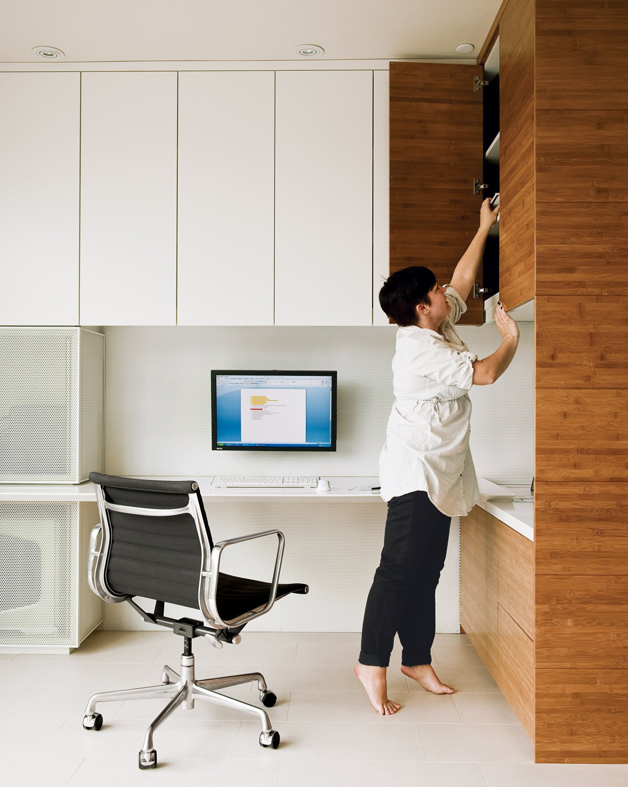 An Eames Aluminum Group chair for Herman Miller and bamboo shelving system are featured in the office Camille Owens and architect husband Francisco created within their living-dining space.