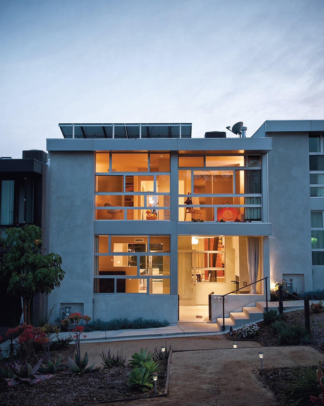 Architects Ana Henton and Greg Williams broke up the uniformity of the seven town homes by making a feature of the Jeldwin dual-glazed windows, laid horizontally here and vertically on the neighboring units.