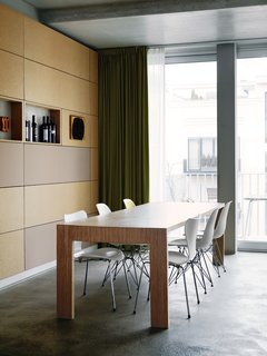 A Rational Approach - Photo 1 of 16 - Next to the kitchen, Eames and Jacobsen chairs welcome dinner guests to the dining-room table. The back wall is covered in particleboard panels.