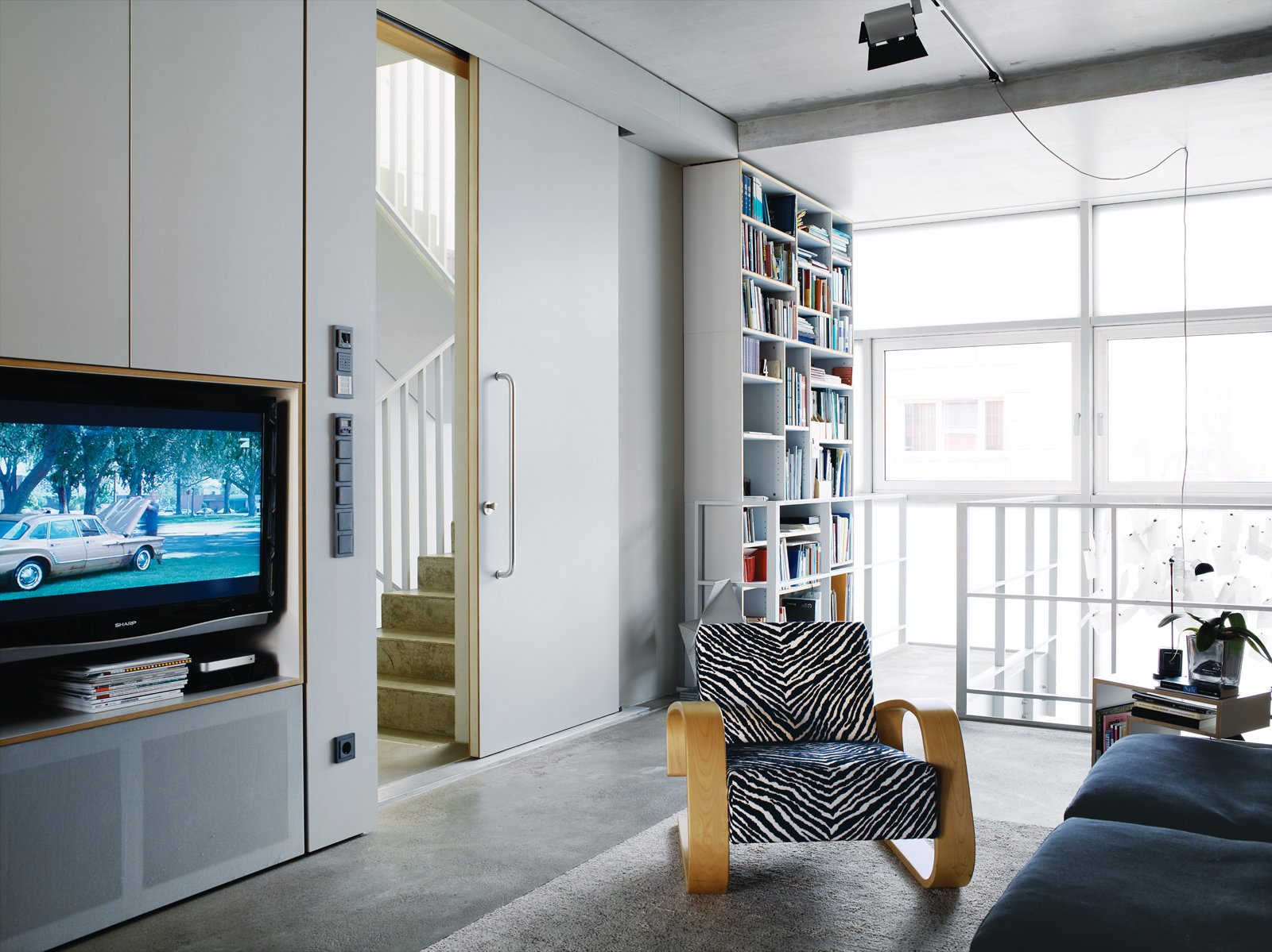 Very large doors, like the one leading from the living area to the stairwell, add to the sense of space. Tagged: Living Room, Chair, Concrete Floor, and Bookcase.  Photo 13 of 16 in A Rational Approach