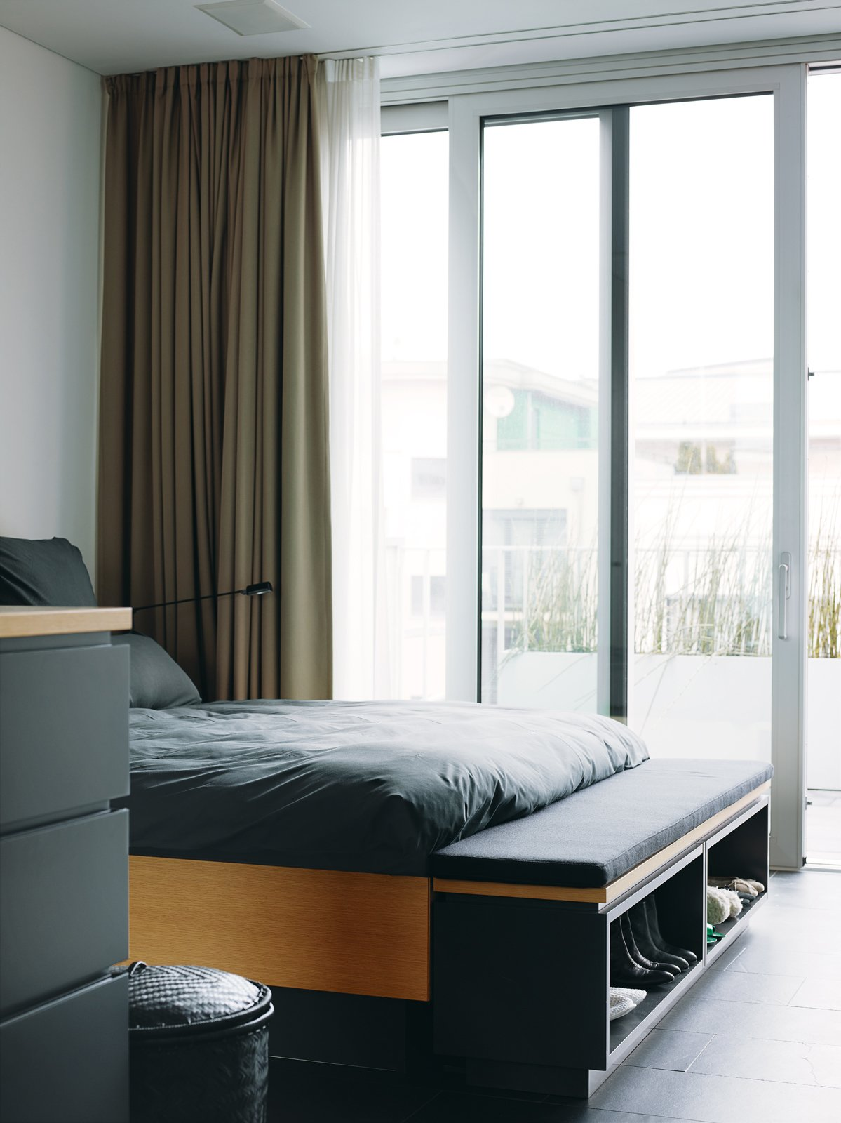 The interior is bright and charming, cool but not cold. Each floor is open, with an unencumbered view from the glass facade in front to the glass doors in back, which makes the rooms feel much larger than they are. Tagged: Bedroom and Bed.  Photo 15 of 16 in A Rational Approach