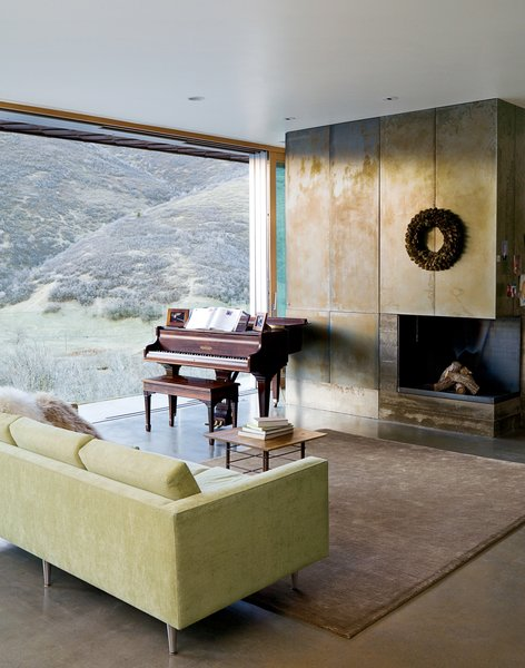 """In the living room, the canyon vistas share center stage with the wood-burning fireplace (attractive despite going through an """"awkward phase"""") and a rare quarter-grand piano from the late 1800s, a Mooney family heirloom. The polished concrete floors are radiant-heated, powered by a small, highly efficient boiler in the basement."""