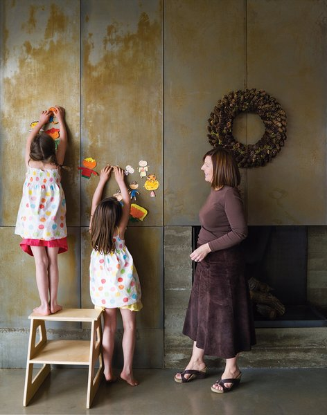 In the living room, Claire and Audrey demonstrate the magnetic quality of their fireplace by hanging artwork next to the wreath.