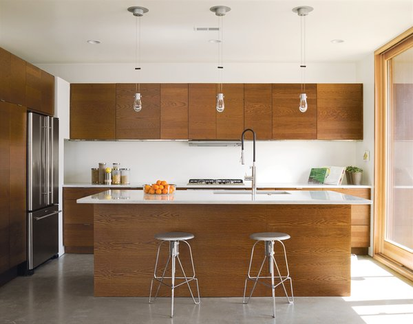 The family's 150-square foot kitchen features Carrara marble countertops—perfect of pasta-making, John says. The stools are the Covey Stools by Jeff Covey.