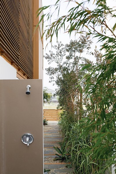 After a day at the beach, an outdoor shower tucked toward the back of the house allows everyone to rinse off without tracking sand indoors.
