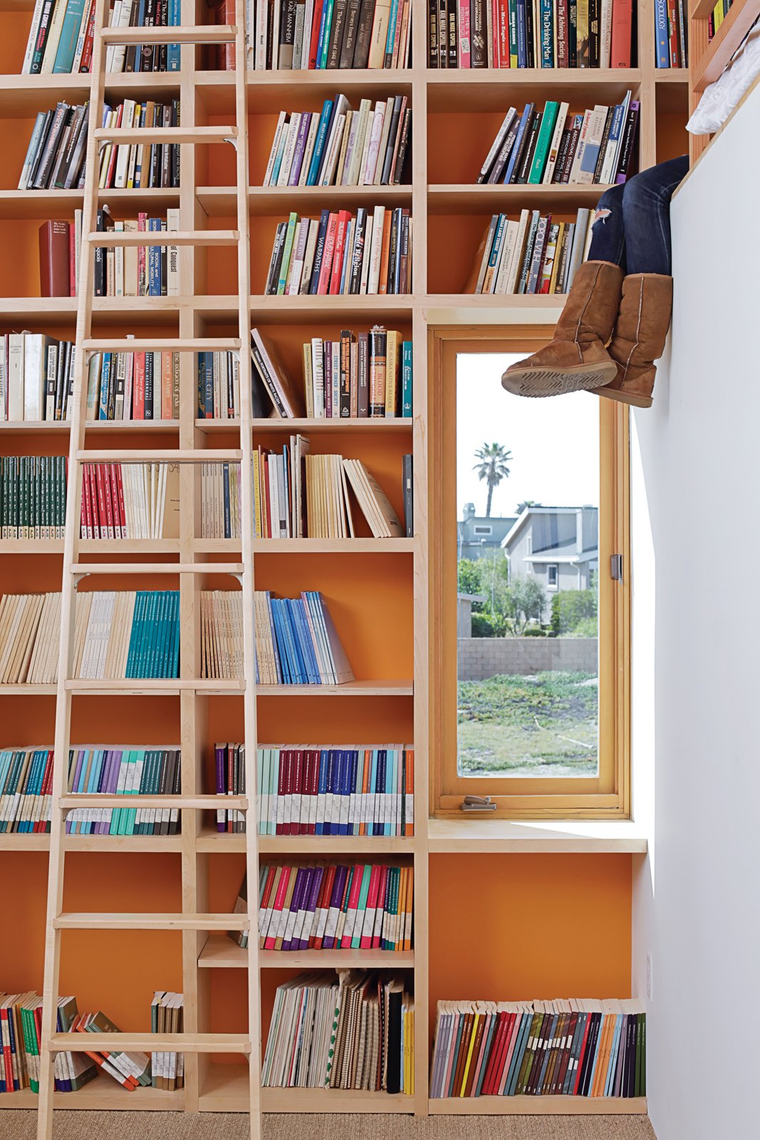 To make the most of 13-foot-high ceilings that help draw hot air out through second-floor windows and doors, designer Daniel Garness painted select walls with playful color and lined them with maple plywood bookcases. Library ladders (about $1,500 each from Alaco Ladder Company) provide access to reading material and a sleeping loft. Tagged: Storage Room and Shelves Storage Type.  Photo 2 of 13 in Coast Docs