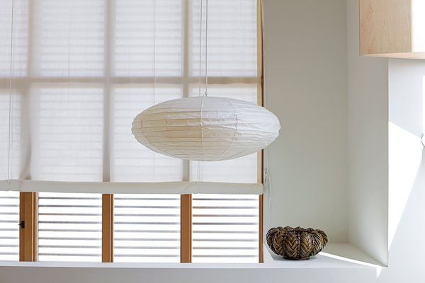 Inexpensive muslin makes a lightweight and luminous covering for windows and the pivoting glass door in the kitchen. While the roll-up shades fabricated by Van Nuys Awning Co. resemble a ship's sails, the hardware for the cords calls to mind boat cleats. Both are fitting nautical references as the house is located only blocks away from the ocean.
