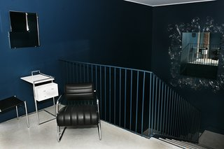 These 9 Spaces Show How to Rock a Monochromatic Color Scheme - Photo 7 of 9 - The dark, moody blue of this area's walls of a furniture showroom and gallery space in Toronto by George Yabu and Glenn Pushelberg are lightened by several mirrors on the walls, and broken up by a metal railing that's painted to match. On the top of the landing sits Eileen Gray's 1935 Bonaparte armchair and Petite Coiffeuse occasional table from 1929, whose chrome legs reflect light and the blue walls surrounding them.