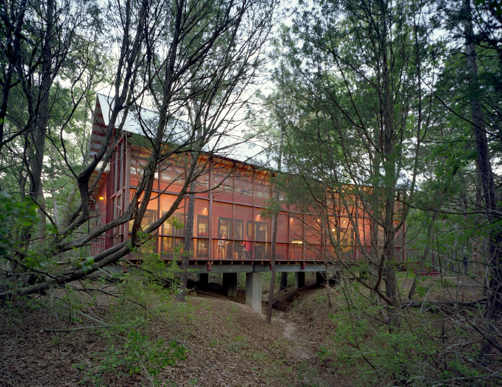 A screen porch runs the entire length of building, built over a dry creek bed on embedded concrete piers. The architect says he worked with the varying topography and native pines, turning the building 30 degrees at one point to accommodate the natural contours of the land.