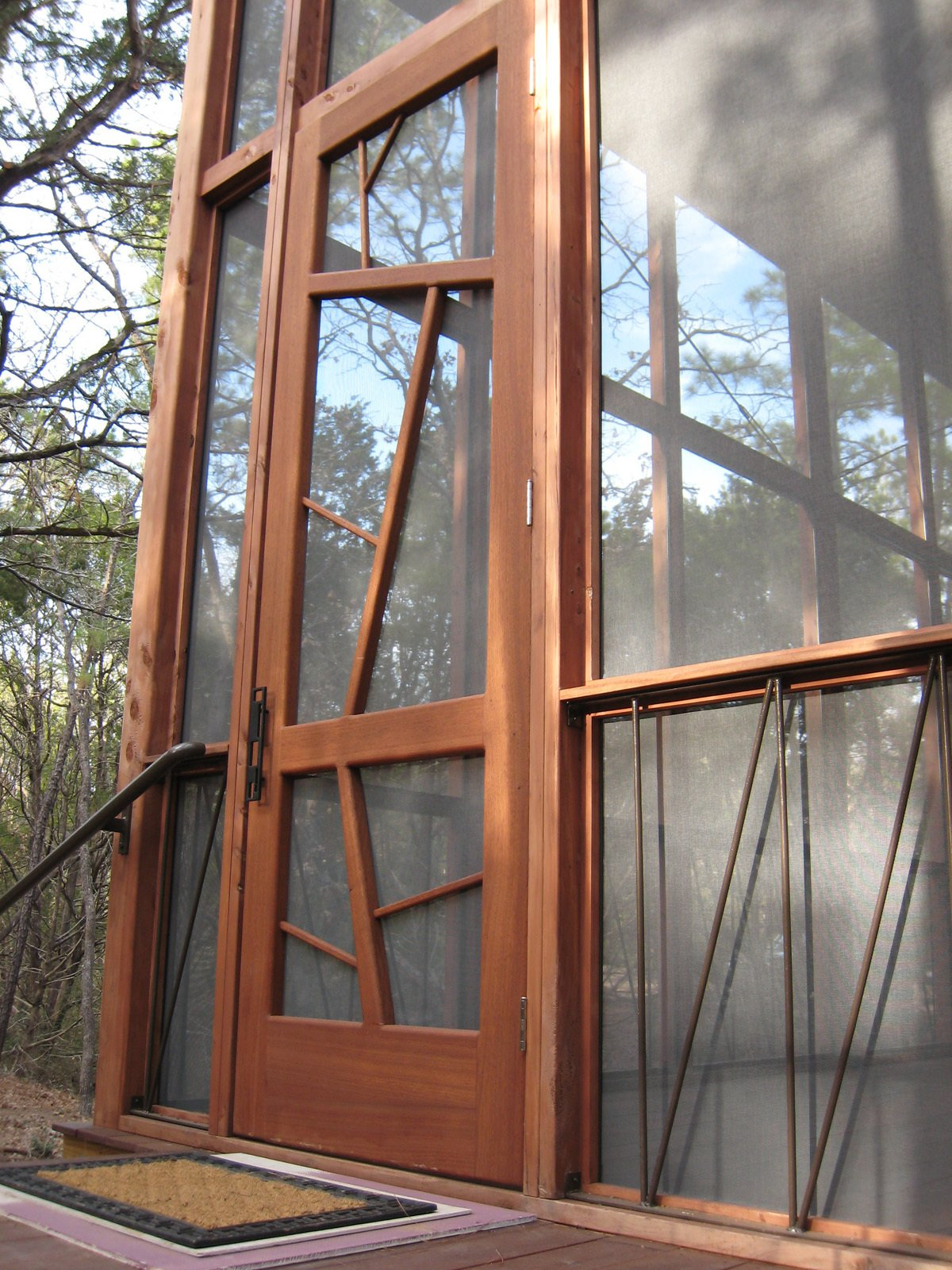 "The nine-by-three-foot mahogany entrance door is meant to evoke the surrounding trees. The iron handrails lining the base of the porch are a subtle architectural detail, as well as a support system to prevent the cabin from ever twisting or shifting ""like so many old Texas outbuildings,"" says Panton."