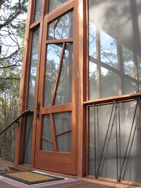 "The nine-by-three-foot mahogany entrance door is meant to evoke the surrounding trees. The iron handrails lining the base of the porch are a subtle architectural detail, as well as a support system to prevent the cabin from ever twisting or shifting ""like so many old Texas outbuildings,"" says Panton. Photo 7 of Texas Bunkhouse modern home"